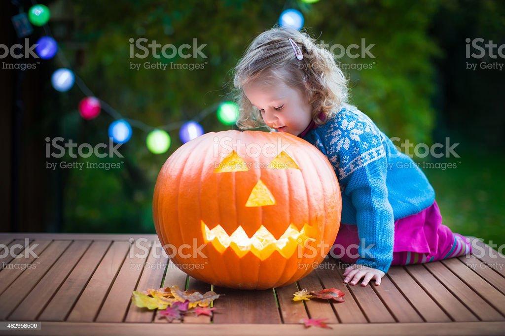 Little girl carving pumpkin at Halloween stock photo