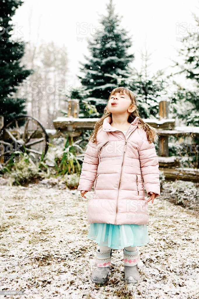 Little Girl Catching Snowflakes on Tongue stock photo