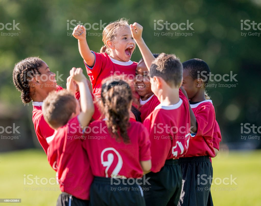 Little Girl Cheering in Team Huddle stock photo