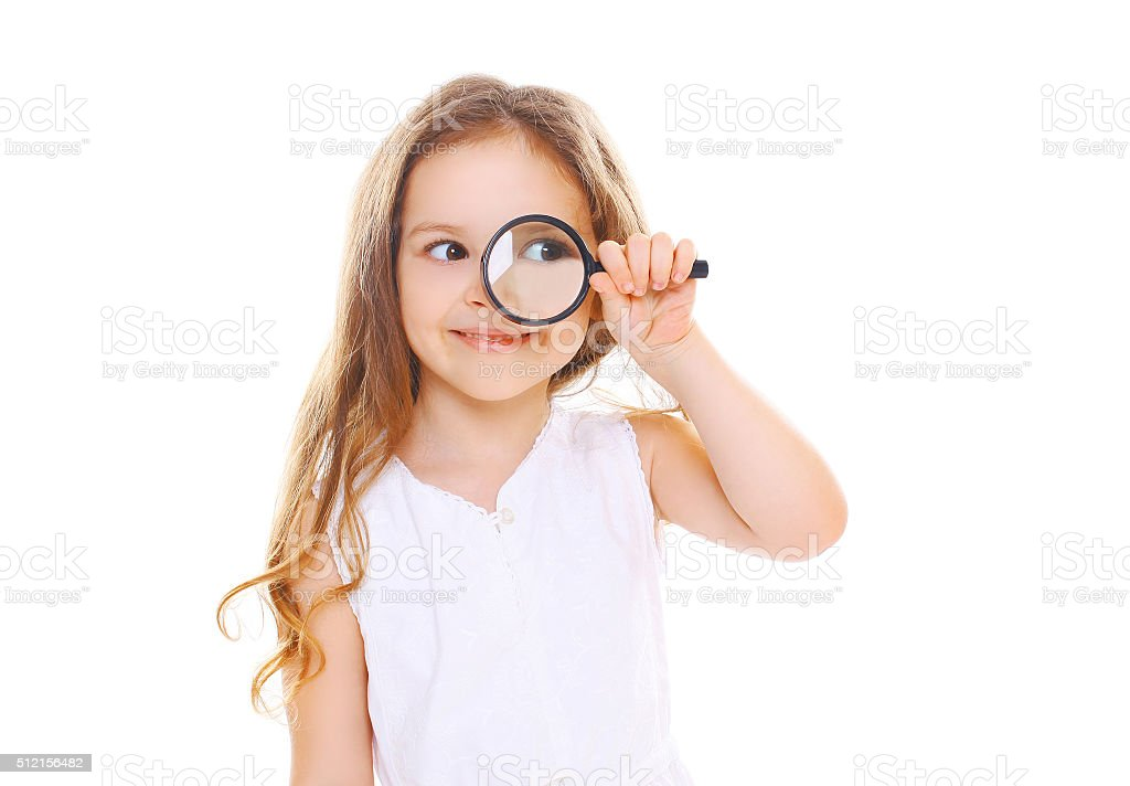 Little girl child looking through a magnifying glass on white stock photo