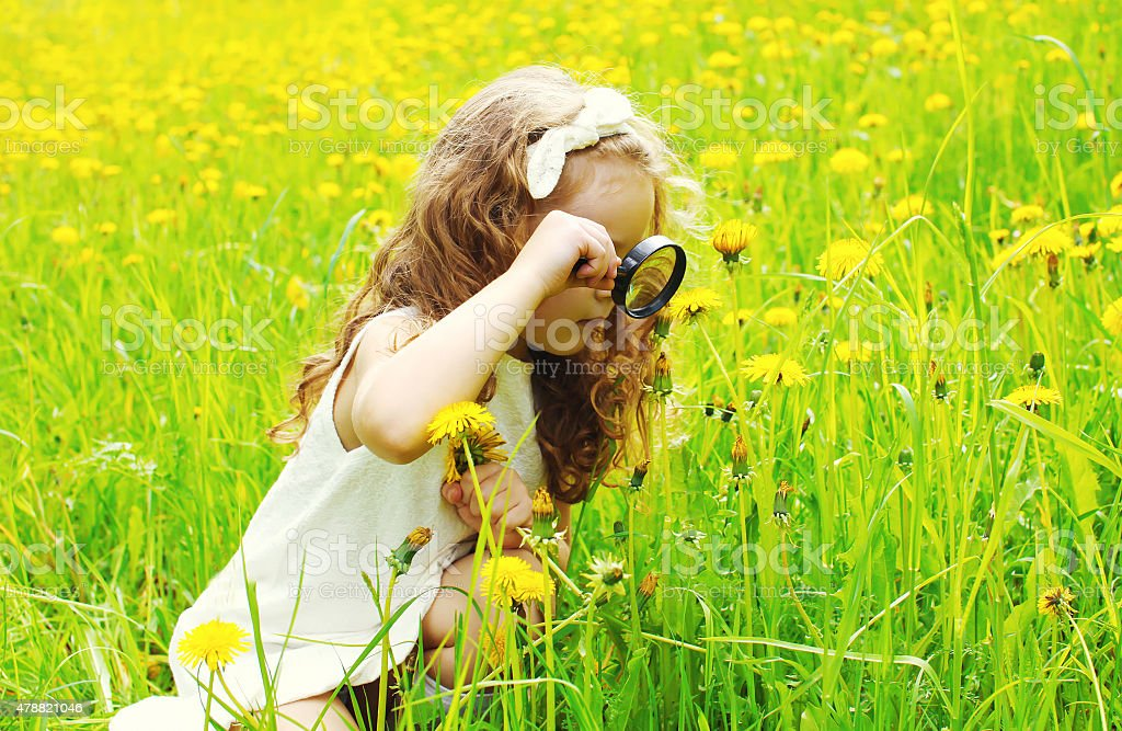 Little girl child looking through a magnifying glass stock photo