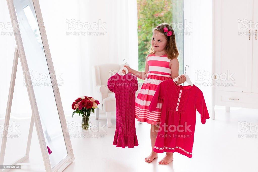 Little girl choosing dresses in white bedroom stock photo