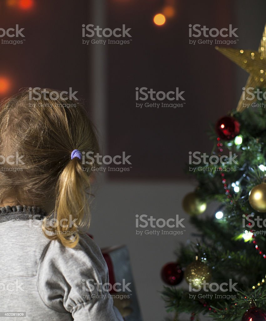 Back view of 3 year old little girl standing near Christmas Tree and...