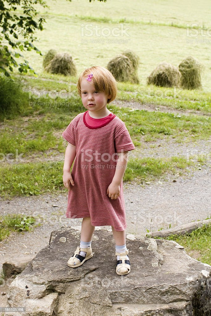 Little girl claiming victory on top o f a rock stock photo