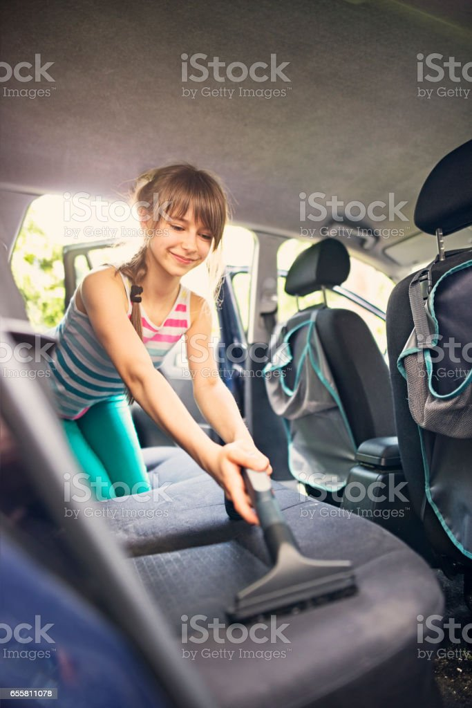 Little girl cleaning car interior stock photo