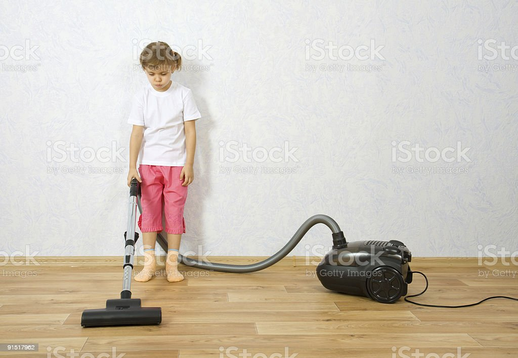 Little girl cleaning floor with vacuum cleaner stock photo