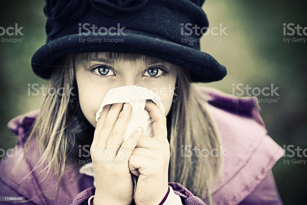 Little girl cleaning nose outdoors royalty-free stock photo