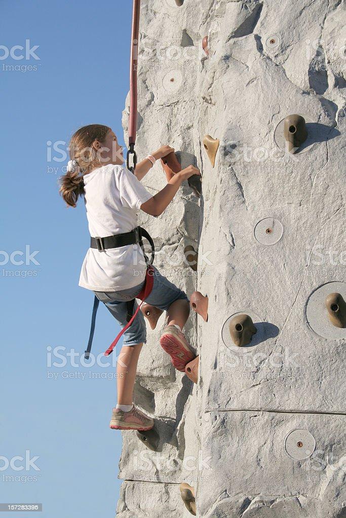 Little Girl Climbing A Wall stock photo