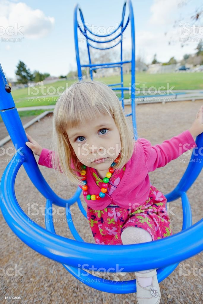 Little girl climbing bars on a playground royalty-free stock photo