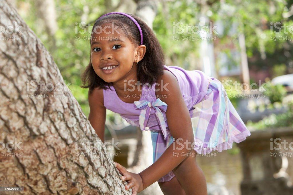 Little girl climbing tree stock photo