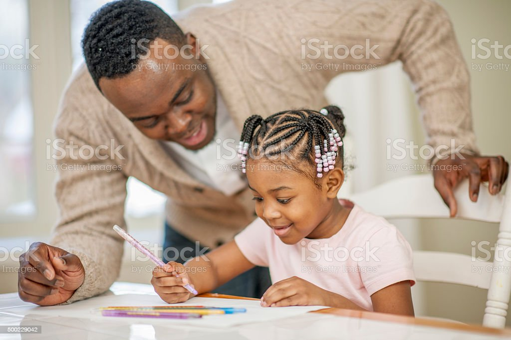 Little Girl Coloring a Picture with Her Father stock photo