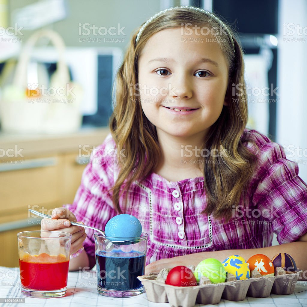 Little girl coloring Easter eggs royalty-free stock photo