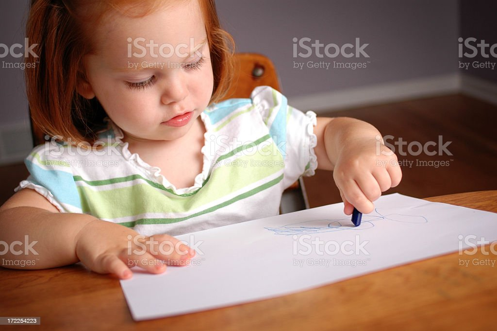 Little Girl Coloring in a School Desk royalty-free stock photo