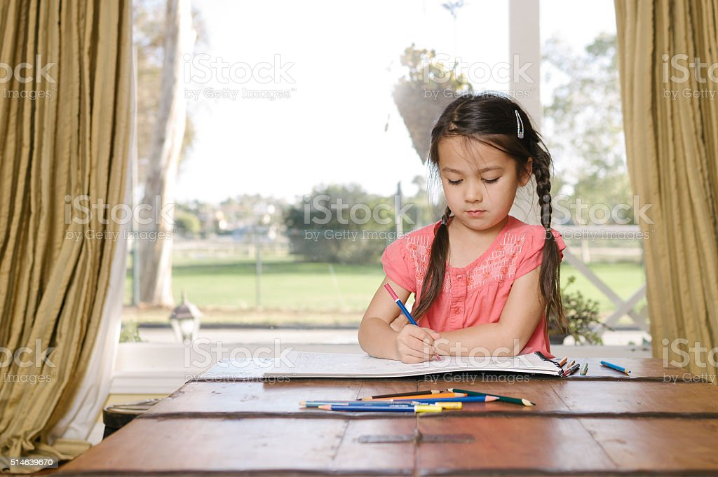 Little girl coloring in with pencils at home stock photo
