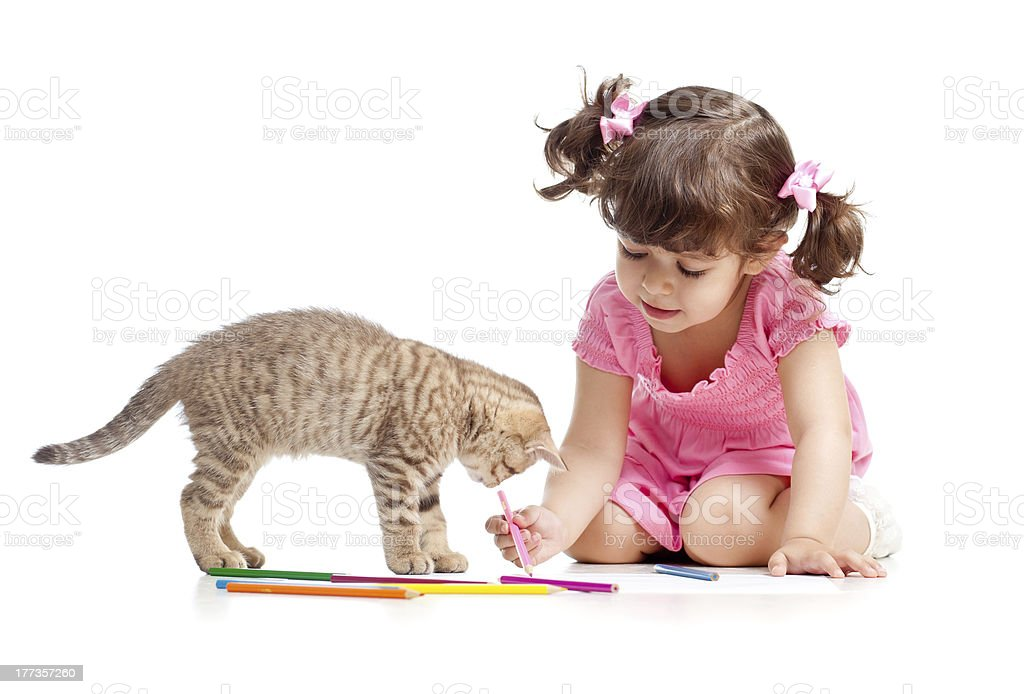 A little girl coloring on the floor while her kitten watches royalty-free stock photo