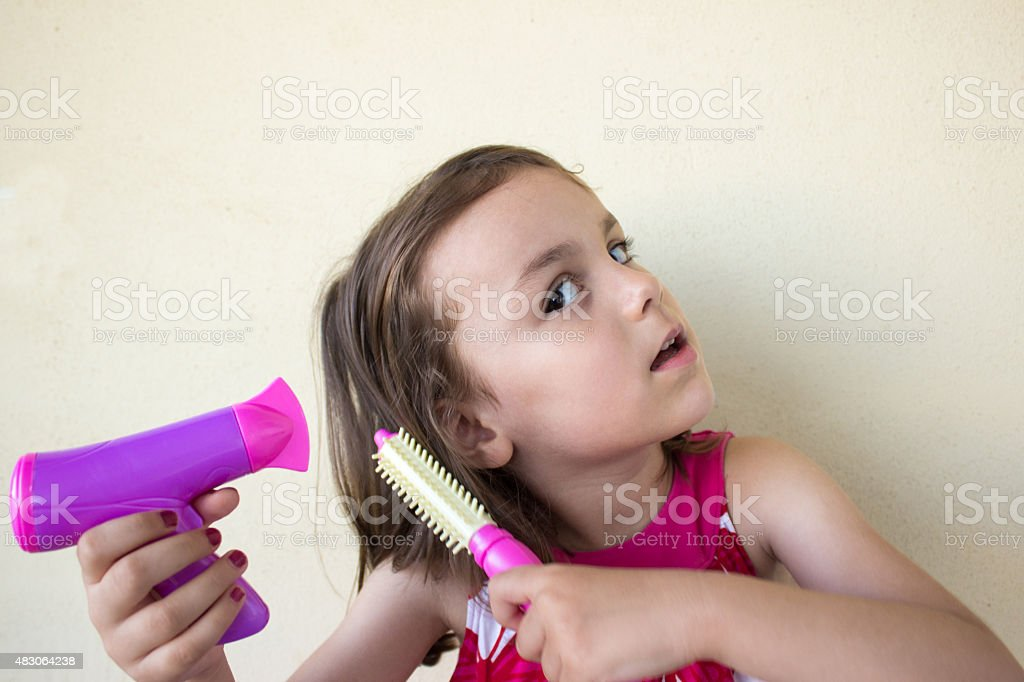 Little girl combing hair and holding a hair dryer stock photo