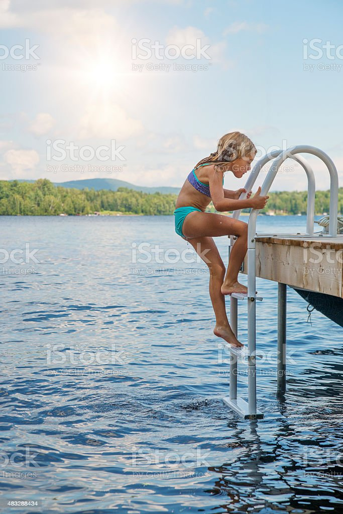 Little girl coming out of lake climbing on pier ladder. stock photo