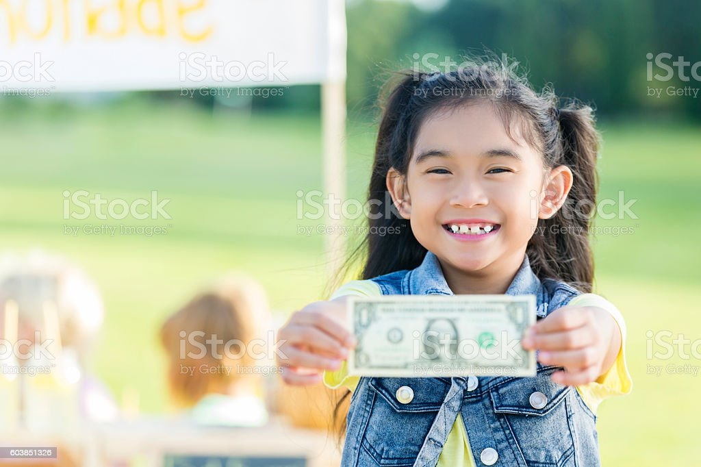 Little girl confidently holds first profit from lemonade stand stock photo