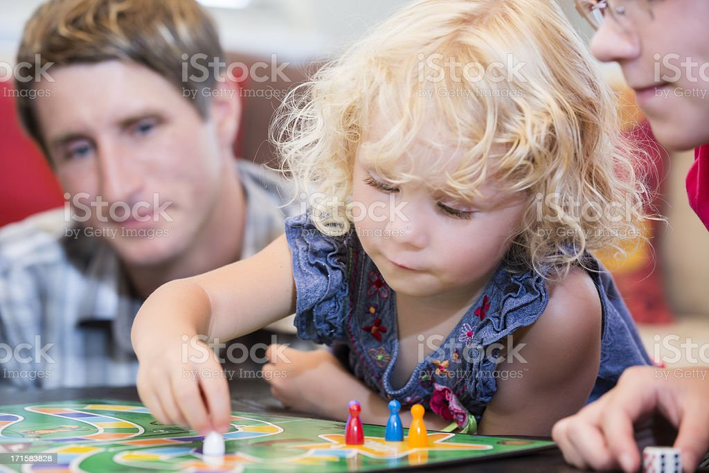 Little girl contemplating her next game move stock photo