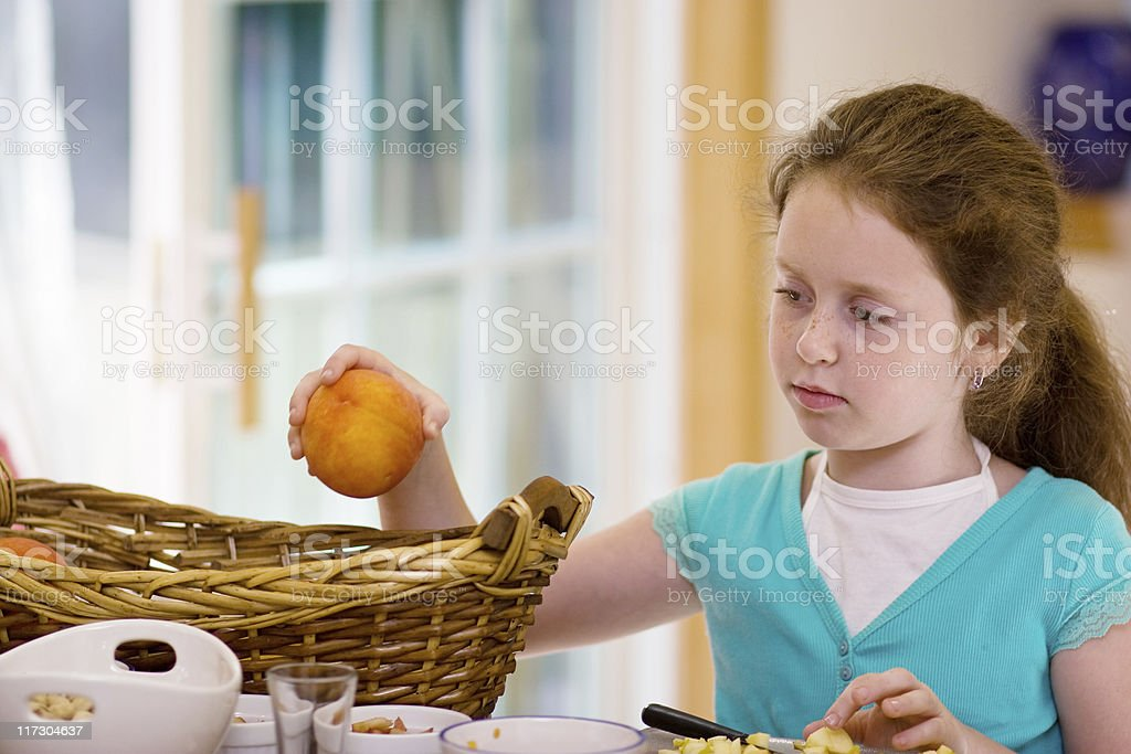 Little girl cook the fruit salad: take peach from basket stock photo