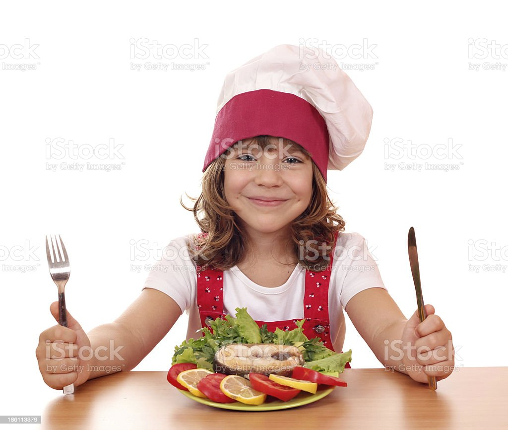little girl cook with salmon seafood on table stock photo