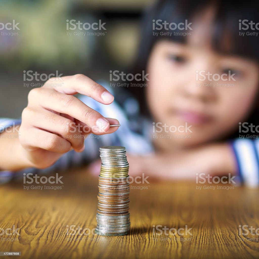 Little girl counts his coins stock photo