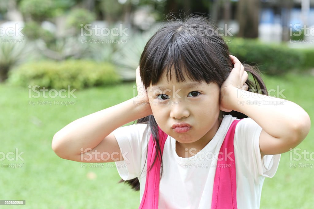 Little girl covering her ears. stock photo