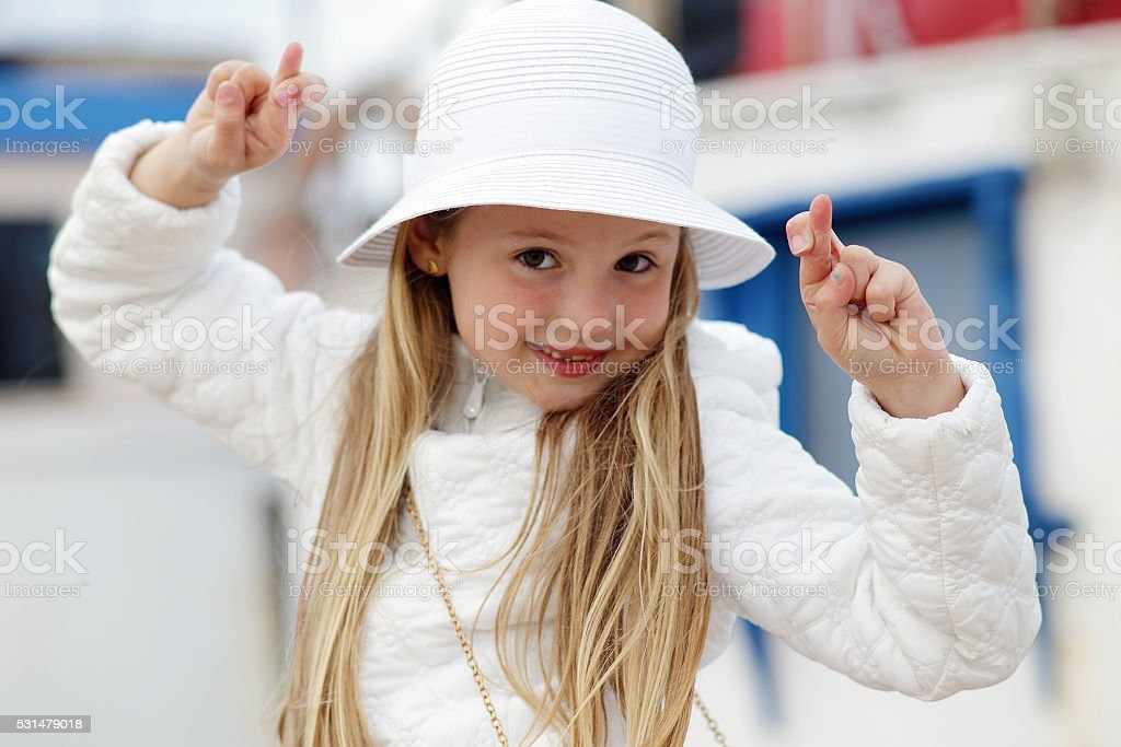 Little girl cross your fingers stock photo