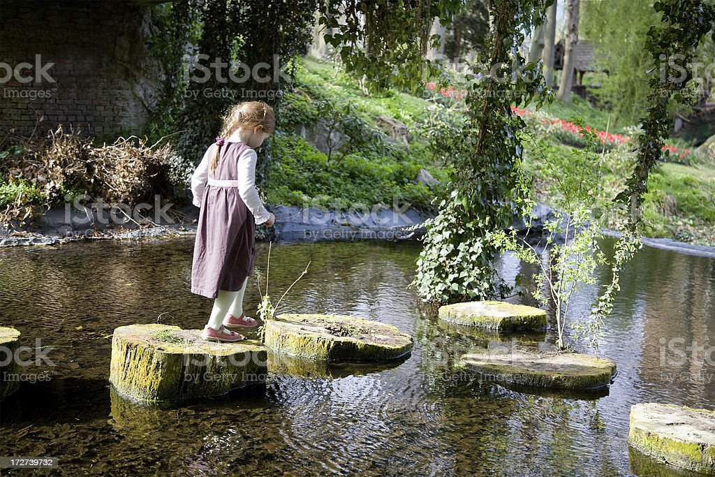 Little girl crossing a pond royalty-free stock photo