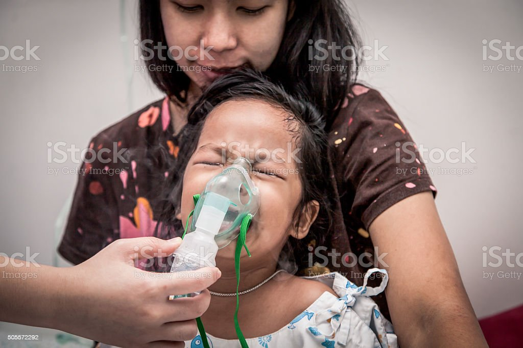 little girl crying while getting in inhaler mask in hospital stock photo