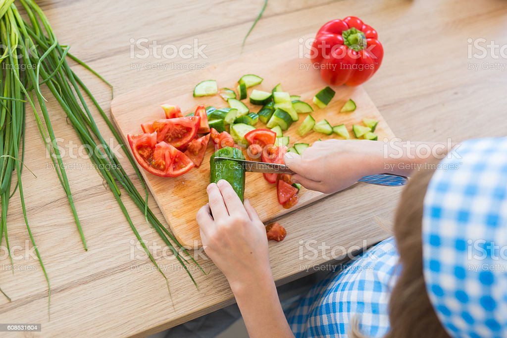 TOP VIEW: Little girl cuts a cucumber on a board stock photo