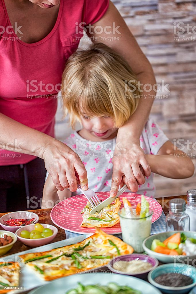 Little Girl Cutting Asparagus Tart with Her Mother stock photo