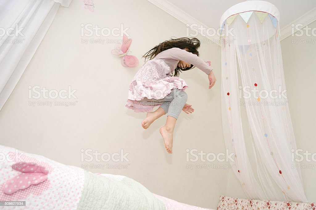 Little girl dancing and jumping on her bed stock photo
