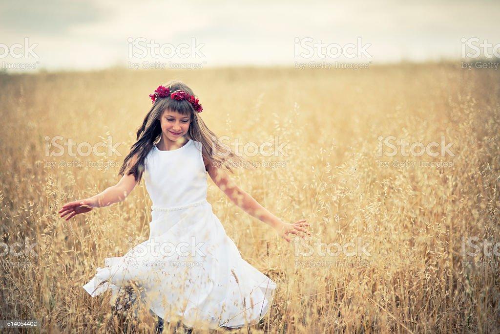 Little girl dancing in grain field stock photo