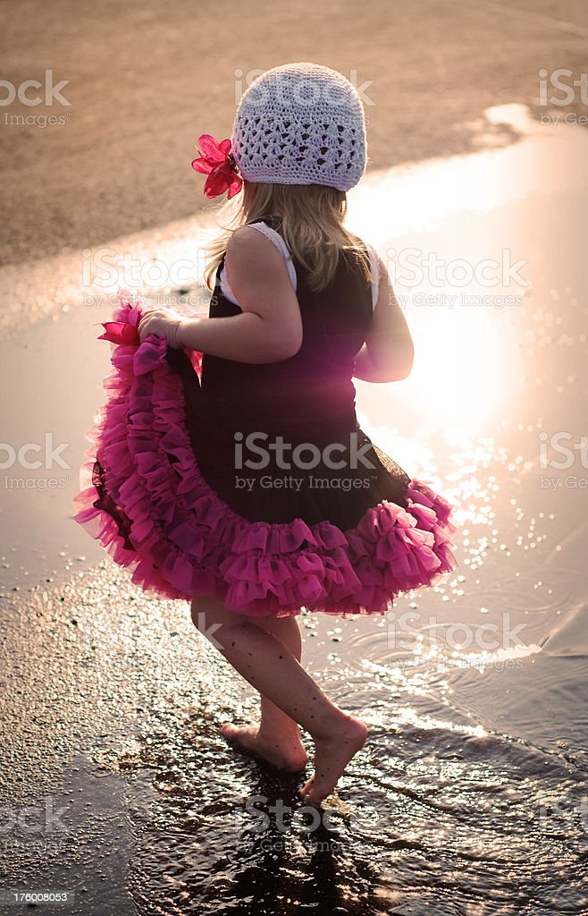 Little Girl Dancing in Puddle Wearing a Tutu and Hat royalty-free stock photo
