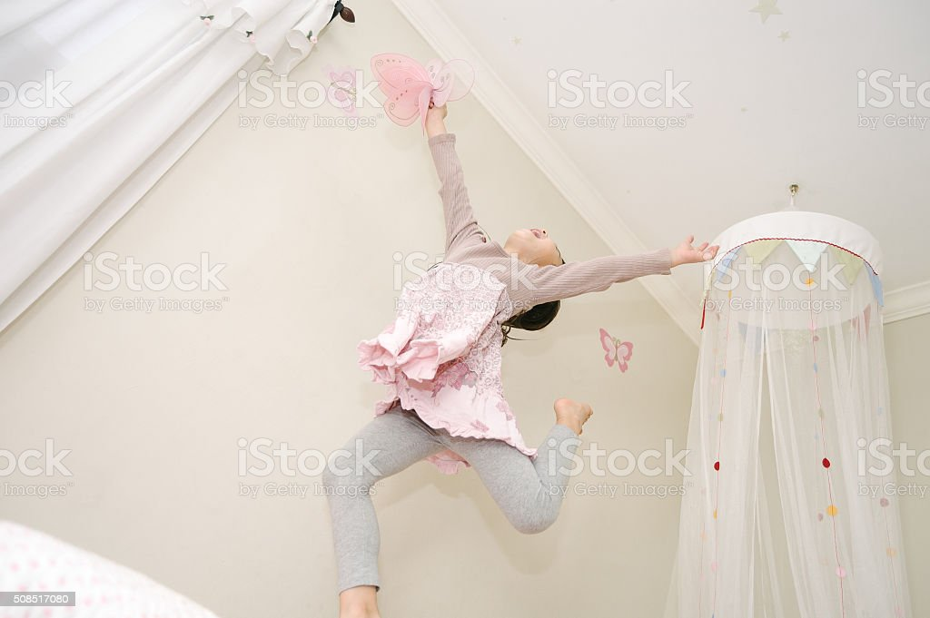Little girl dancing on her bed with a butterfly stock photo