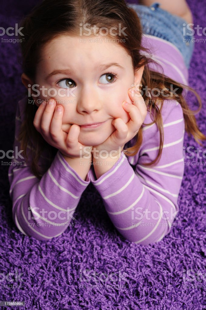 Little Girl Daydreaming While Lying on Purple Carpet royalty-free stock photo