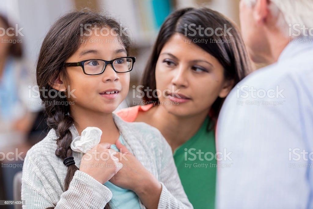 Little girl describes symptoms to emergency room doctor stock photo