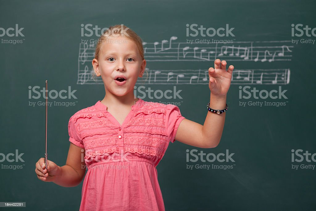Little Girl Directing Chorus For Folk Music Before Blackboard stock photo
