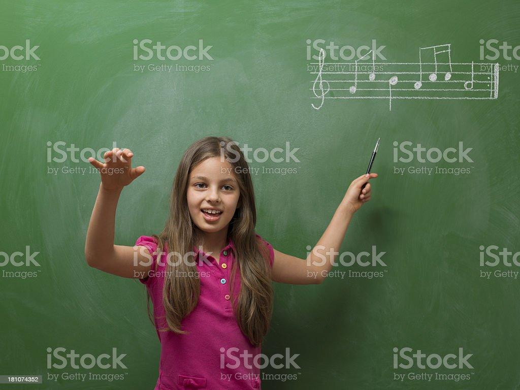 Little girl directing chorus for music before blackboard royalty-free stock photo