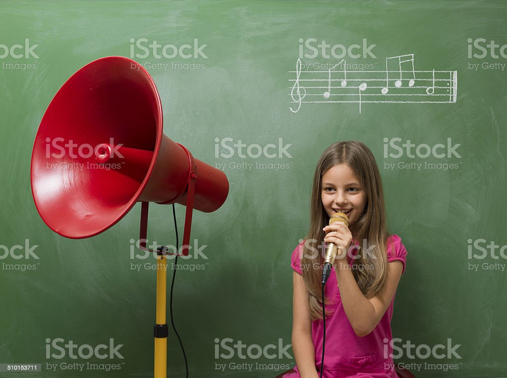 Little girl directing chorus for music before blackboard stock photo