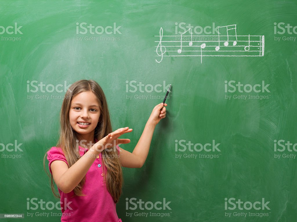 Little girl directing chorus for music before blackboard stock photo