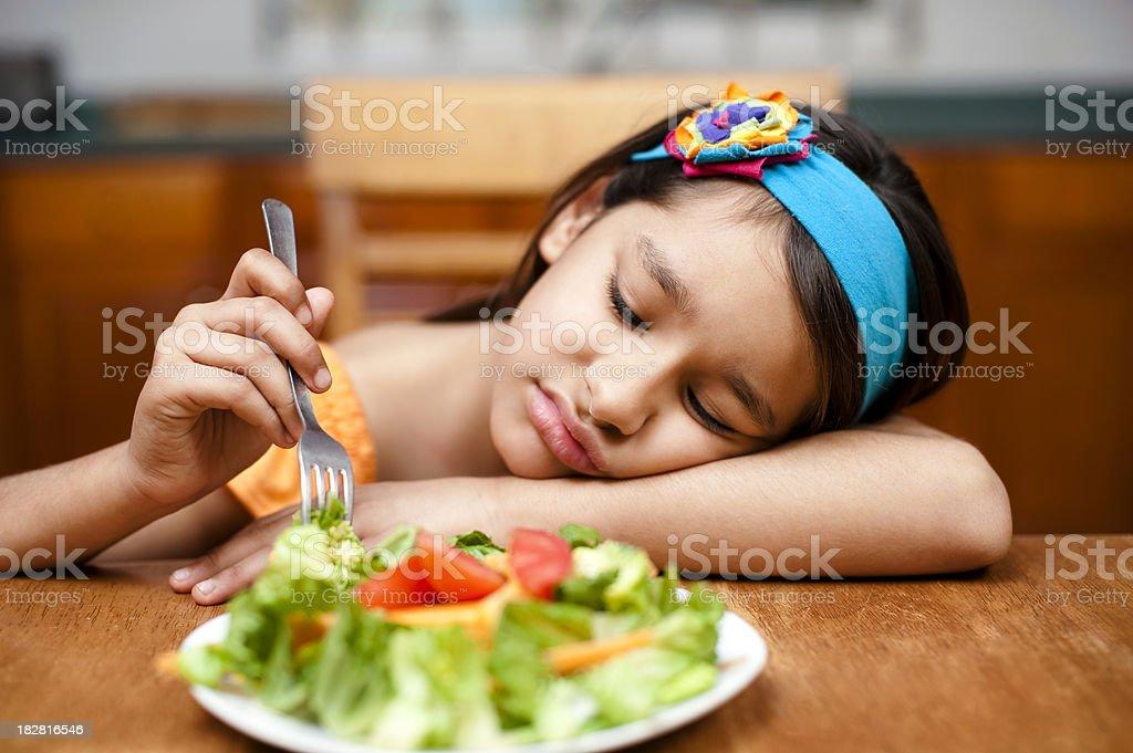 Little girl disliking her salad stock photo