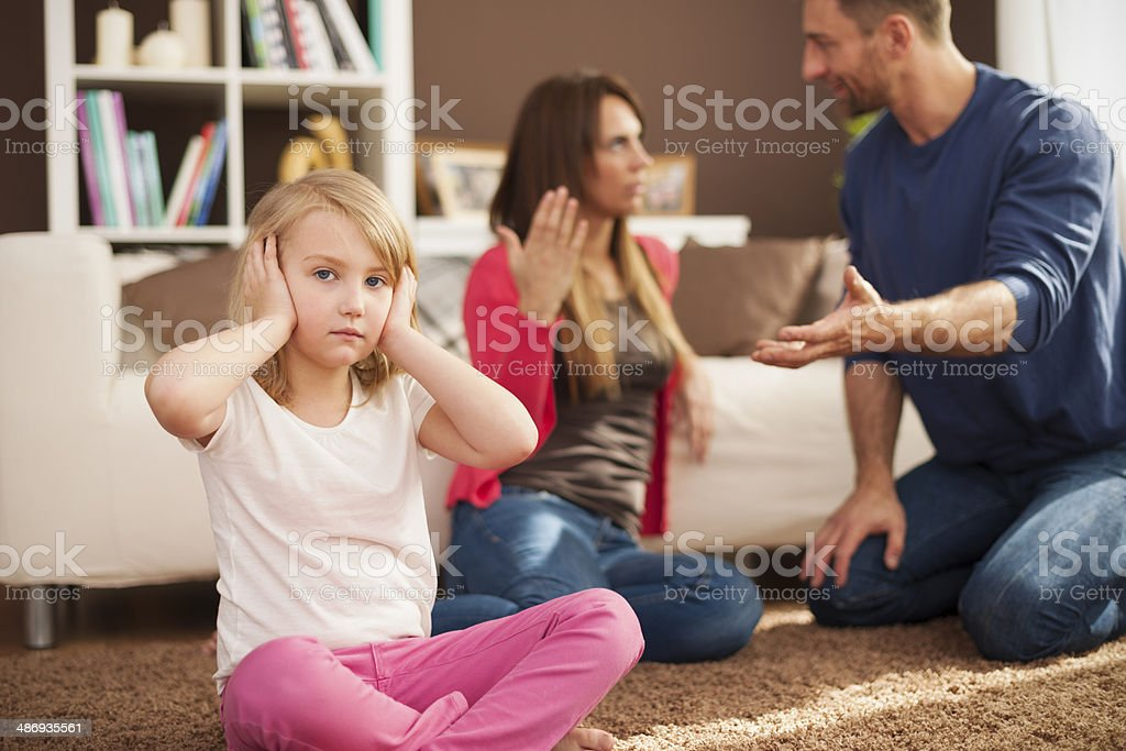 Little girl doesn't want to hear arguing of parents stock photo