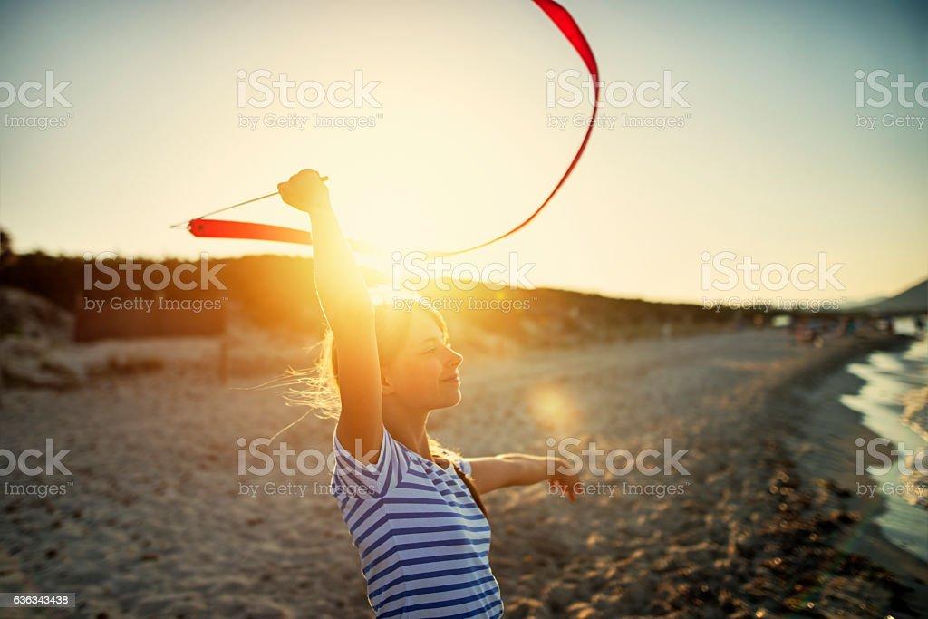 Little girl doing gymnastics on the beach. stock photo