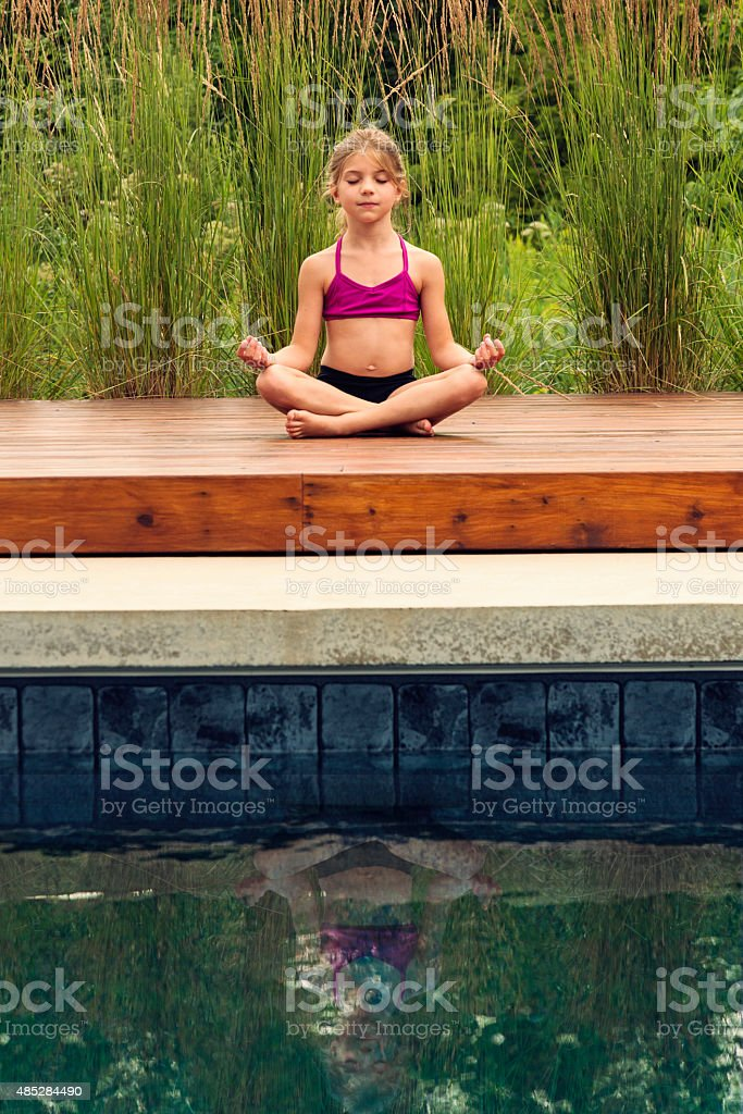 Little girl doing yoga outdoors in summer nature. stock photo