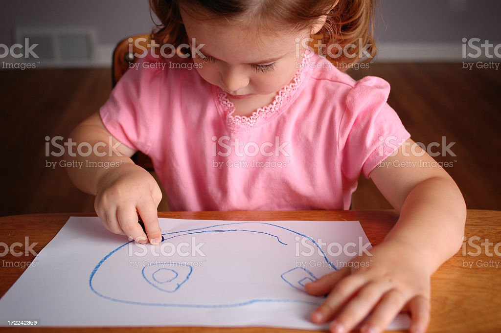 Little Girl Drawing a Happy Face on Paper royalty-free stock photo