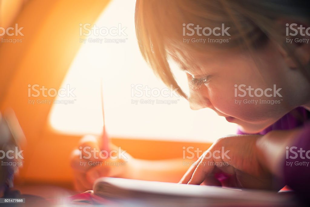 Little girl drawing by the window stock photo