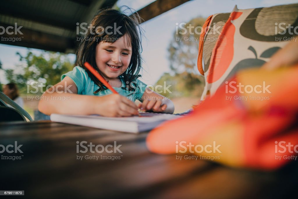 Little Girl Drawing in a Colouring Book stock photo