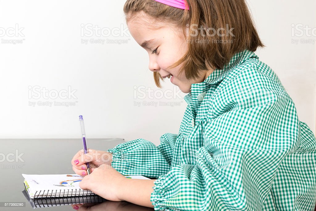 Little girl drawing in a notebook stock photo